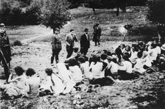 German police and auxiliaries in civilian clothes look on as a group of Jewish women are forced to undress before their execution.