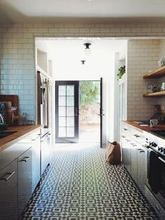 Neutral white modern kitchen with wood counters, subway tile and patterened tile Floors
