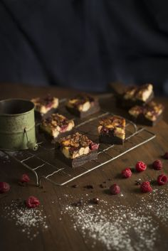 chocolate raspberry cheesecake brownies...served on white platters with fresh raspberries for garnish.