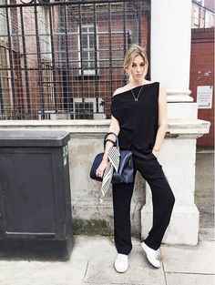 Camille Charrière of Camille Over the Rainbow wears an off-the-shoulder jumpsuit, white sneakers, a dainty necklace, and a satchel with a scarf