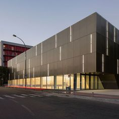 Bands of light shine through the perforated metal facade of this sports hall.: