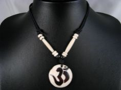 Beau collier composé d'un galon noir et d'un pendentif en os de buffle, avec le symbole Om. ------------------------------------------------- A bone necklace with Om in sanskrit carved in the middle. www.savdana.com