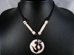 Beau collier composé d'un galon noir et d'un pendentif en os de buffle, avec le symbole Om. ------------------------------------------------- A bone necklace with Om in sanskrit carved in the middle. www.savdana.com