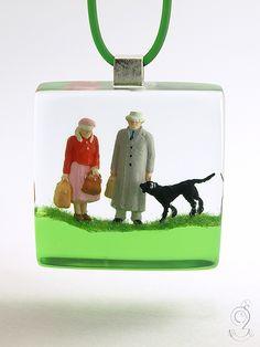 Joe & friends – Goldiger Figuren-Anhänger mit zwei Reisenden auf mittelgrünen Boden mit Gras und Hund in Gießharz   ///// © Isabell Kiefhaber www.geschmeideunterteck.de