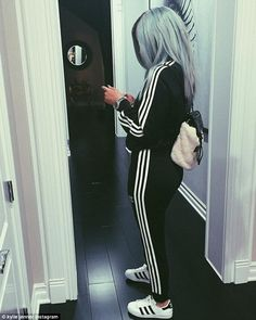 Sporty: The 17-year-old star is seen clad in an Adidas tracksuit in another snap ...
