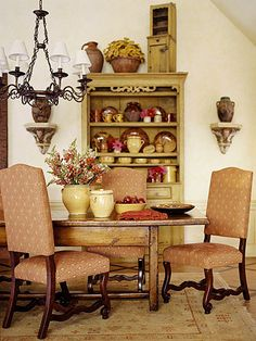 Rustic Sensibility        In the dining room, new upholstered dining chairs surround a chestnut table. The hutch is from Provence and features its original mustard-color paint finish. Colorful red and yellow pottery fills the shelves with Country French style!