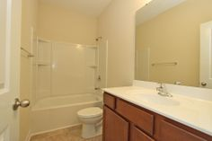 This guest bathroom features medium brown wooden cabinetry by Aristokraft.