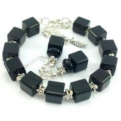 Komplet biżuteriidamskiej wykonany ręcznie. Kolczyki i bransoletkaz czarnych koralików szklanychkostek i elementów w kolorze srebrnym. Ozdobne elementy w kształcie gwiazd.
