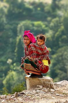 Nepal. Innocent with the colors of culture and sitting on a dominated stone.