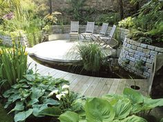 The wooden walkway, circular terrace and snaking wall pair perfectly with hostas, irises, grasses and marginals.