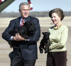 President George W. Bush and first lady Laura carry their Scottish Terriers, Barney and Miss Beazley.