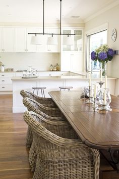 kitchen with white cabinets beige counters and wrought iron details with wicker and rustic wood rattan dining chairstable