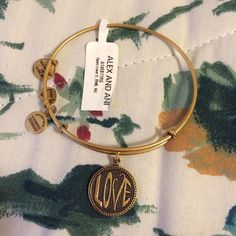 Alex & Ani Gold Love Bangle Brand New With Tag! ⛔️ NO TRADES, NO PAYPAL, NO MERCARI, NO HOLDS ⛔️ smoke free, pet free home  let me know if you have other questions  PLEASE MAKE OFFERS THROUGH THE OFFER BUTTON. Alex & Ani Jewelry Bracelets