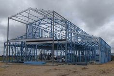 'American' barn under construction showing c-section portal frames with steel stud framing between.