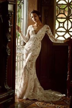 """Sultry brides look no further! This dramatic lace sheath is one your guests will never forget!  4"""" extra length gown.  Allover lace paired with nude fabric gives the illusion of a nude gown.  Long lace sleeves provides glamarous coverage of shoulders and arms.  Deep v-neckline accentuates the bustline, while low back adds sultry detail.  Sweep train. Sizes 0-16.  Available in Ivory/Nude by special order only in stores and online.  Fully lined. Back buttons. Dry clean only.  Missy: Style"""