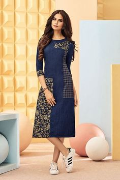 Step in style as you don this sassy blue denim kurti featuring yellow floral print patches over the right side flare & left side top of torso, left side panel bearing another stylish print & fancy gold dots decorating the outline of neckline and bust patch in a striking glam!