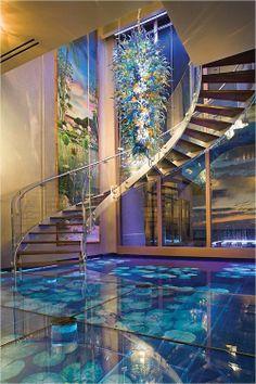 una gran sala de acuario por las escaleras con todo tipo de pescados