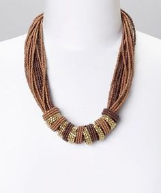 A carefully cultivated ensemble needs a statement accessory to finish the look. Featuring lovely layers of beads cinched by lustrous rings, this necklace exudes unique style.