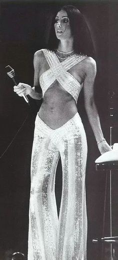 Cher, 1970s. White and sequin bell bottom pants with a criss cross top.