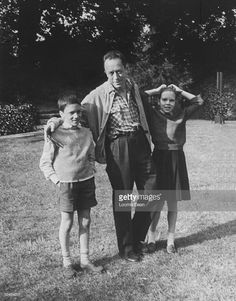 French author Albert Camus poised standing on lawn, arms around his twins Jean & Catherine.