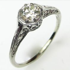 Lemon Drop: A diminutive but detailed solitaire ring, centered on a beautifully cut antique diamond of palest lemon yellow. Ca.1935. Maloys.com