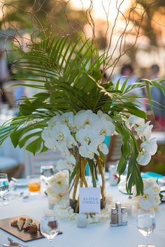 Tropical Wedding Centerpiece with Palm Leaves, Monstera Leaves, White Orchids and some Branches for height. Beautiful way to bring a touch of Maui to your elegant wedding. Tropical Wedding Centerpieces, Orchid Centerpieces, Centerpiece Ideas, White Orchid Centerpiece, Tropical Wedding Decor, Centerpiece Flowers, Hawaiian Centerpieces, White Orchid Bouquet, Tropical Wedding Bouquets