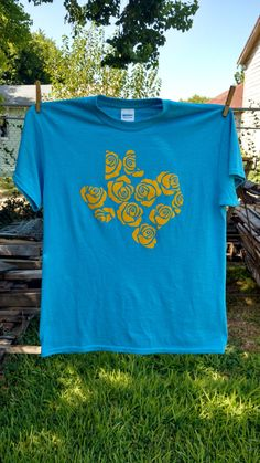 Yellow Rose of Texas.Anyone that loves Texas knows about the yellow rose of Texas. This is a heathered blue t-shirt with yellow HTV vinyl. It is pre-shrunk in a poly/cotton blend. Free domestic shipping on all of our t-shirts! Texas Tshirt, Yellow Roses, Cotton, Mens Tops, T Shirt, Blue, Etsy, Supreme T Shirt, Tee
