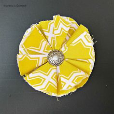 Cut 6-10 circles from your fabric. Mine are about three inches wide.     Fold your circle in half with the print showing.    Fold the right corner up to the middle.    Repeat with the left corner.     Use your needle and thread to join each petal so they overlap slightly.     When you are done attach the button or beads by sewing on.    Use E6000 to glue a hair pin blank to the back. (I purchased the pin blanksand the headband from Pick Your Plum!)