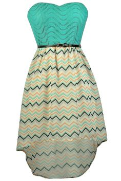 FINAL SALE. This fun chevron high low dress has so many details that make it adorable! The High Low Times Teal and Orange Chevron Belted Dress is fully lined to the mid-thigh. It has a strapless sweetheart neckline and lightly padded bust. The top of this dress is made of a teal crochet fabric. The attached skirt is made of a flowy fabric with an ivory, orange, green, and black chevron print throughout. The skirt has a high low cut. An included black belt wraps around the waist, tying this…