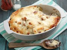 Scalloped Potatoes and Ham : Beneath that gooey layer of melted Monterey Jack cheese lies tender potatoes layered with diced ham and plenty of creamy sauce. Ree notes that it's best to use a mandoline or a sharp knife to slice the potatoes thinly; this will help ensure evenly cooked results.