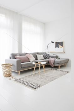 white floor, white walls, grey sofa, grey rug