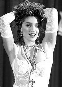 """Madonna's """"Like A Virgin"""" look - create this style with long, fingerless white lace gloves, white bustier, beads necklaces, crucifix necklace and a tutu petticoat skirt."""