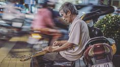 """A busker plays slide guitar as traffic goes by. Ho Chi Minh City Vietnam Go to http://iBoatCity.com and use code PINTEREST for free shipping on your first order! (Lower 48 USA Only). Sign up for our email newsletter to get your free guide: """"Boat Buyer's Guide for Beginners."""""""