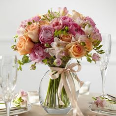 The stunning arrangement in soft shades of pink and orange creates a sweet centerpiece to accent your tables on your wedding day.