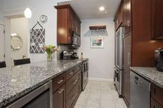 Traditional galley kitchen with salt and pepper color granite and brown cabinetry