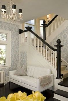 damask entryway foyer.what i like: glossy black floor and hand rails. risers painted white. seating. damask wallpaper is not overpowering. little back shades on chandelier. spindles are painted white. not digging the large white space behind couch.