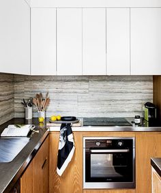 "The 'hero' splashback influenced all the remaining design decisions including the oak cupboards doors and floors, the pared-back and serviceable stainless-steel benchtops, as well as the white wall cabinets, which blend into the skillion roof.   Ocean Blue Travertine **tiles** in Honed finish from [Lapege](http://lapege.com.au/|target=""_blank"")."