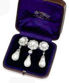 A SUPERB NATURAL PEARL AND DIAMOND BROOCH. Composed of three natural pearl and old-cut diamond clusters, each suspending a natural drop-shaped pearl with rose-cut diamond cap, the central detachable pearl drop with old-cut diamond surmount, mounted in silver and gold, circa 1870, 6.0cm long, in original brown leather fitted case by Garrard & Co.