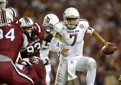COLUMBIA, SC - AUGUST 28: Kenny Hill #7 of the Texas A&M Aggies rols out under pressure from the South Carolina Gamecocks defense during their game at Williams-Brice Stadium on August 28, 2014 in Columbia, South Carolina. Texas A&M won 52-28. (Photo by Grant Halverson/Getty Images)