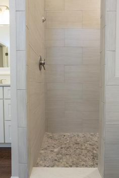 HGTV invites you to see this gray tile shower with beautiful pebble tile floors.