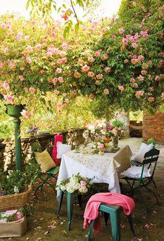 Comedor de exterior con sillas de hierro verde bajo pérgola cubierta de rosas_00365587b. Comedor de exterior con sillas de hierro verde bajo pérgola cubierta de rosas_00365587