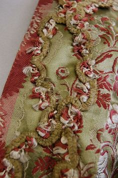 A brocaded satin open robe the fabric late 1760s-early 1770s, the sage green ground woven with pink and ivory feathery bands and blooms, chenille braid to the engageants and front robings,