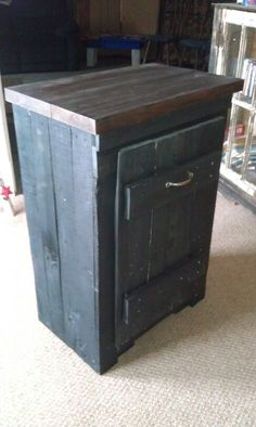 Pallet material trash cabinet with blackwash finish.