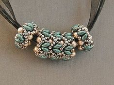 This beautiful beaded bead is part of a design by Ellad2 (Kyra Bangle). I love the texture of this bead. It is 0.75 long, 0.5 wide and 0.5 deep. The hole of the bead is about 0.20 wide. The technique used is netting. The pearls Ive used are platinum color. The Superduos are white pastel patrol. The seed beads are silver and patrol. Its very light and can work with most chains. You can wear it separately, with other beaded beads or you can also use beaded spacers like shown in one of the…