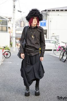 This is Masaya, a 21-year-old guy with an all black gothic-meets-steampunk look. Masaya's shirt is from ankoRock, worn with a deconstructed skirt (or pants). His tote bag is also from ankoRock and his lace-up boots feature heels. He accessorized with a Sexpot Revenge studded belt, a handmade steampunk necklace, a studs choker, a GALUCKTONE steampunk ring, and an ankoROCK furry hat. Masaya's favorite band is The Gazette.