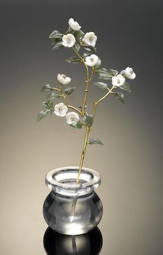 Japonica Flower Study By Georg Wild Idar-Oberstein, Germany Of classic form, with flowers carved from white chalcedony, centering on tiny diamonds set in gold. The leaves are carved of jade, the stem is fabricated of 18K gold emerging from a vase carved of a single quartz crystal giving the illusion of water in the transparent vase. This is a re-creation of a Fabergé work pictured in the book on Fabergé by Kenneth Snowman (Plate 300). Height 6½in
