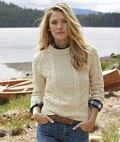 Ivory cable knit sweater over plaid button-down, braided leather belt.