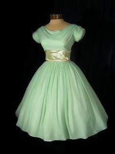"Gorgeous 60s dress is the perfect ladylike vintage look for a prom or wedding. Mint green silk chiffon over matching taffeta. Draped boat neckline that dips lower in the back.Short ruched sleeves. Wide inset champagne satin waistband. Attached matching satin bow with center rosette and trailing satin ribbons.Full gathered skirt with attached ruffled tulle slip Label reads- ""Lorrie Deb San Francisco""Back metal zipper closure"