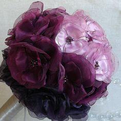 Mooie alternatieve boeket beschikt over meer dan 25 handgemaakte bloemen in variërende tinten paars, magenta en lavendel creëren een prachtige ombre-effect. Elke bloem bestaat uit lagen van satijn en organza die zorgvuldig kaars-geschroeid zijn en elk beschikt over beading in het