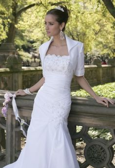 Strapless taffeta mermaid wedding dress with diagonal gathers and beaded lace applique. Bolero included.